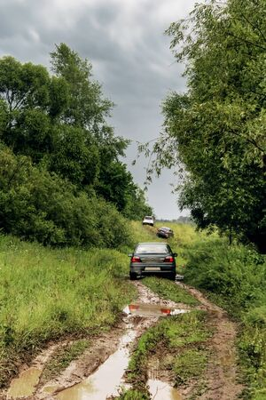 Cars drive along a dirty forest road after rain against the backdrop of a summer landscape, the car got into a puddle, in Russia while traveling