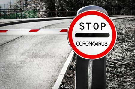 Concept of coronavirus quarantine. Coronavirus written on stop sign on the control barrier at the entrance to the natural park, the habitat of bats. blocked roadway, control