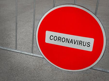 Coronavirus written on stop sign on the control barrier at the entrance to the natural park, the habitat of bats. blocked roadway, control