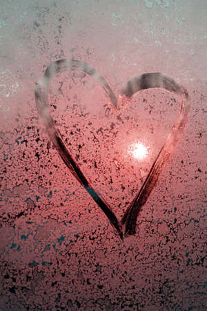 Pink Heart drawn by a finger on misted frosty glass with sun glare, a symbol of happy love, strawberry heart, a message of love, Valentine's Day