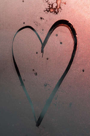 contour of Heart drawn with a finger on pink misted frosty glass with sun glare, symbol of happy love, strawberry heart, message of love, Valentine's Day