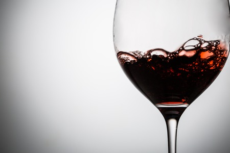 Red wine with bubbles in wineglass. Image closeup with space for your text