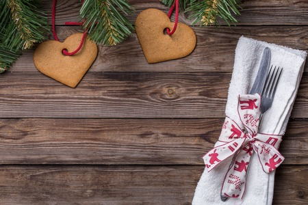 grunge silverware: Christmas table place setting with fork and knife,decorated ribbon and bow, christmas pine branches and cookies. Christmas holidays background. Stock Photo