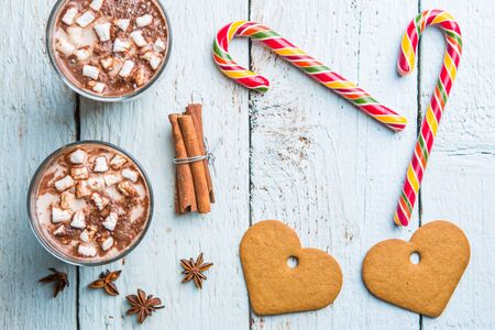 Christmas decor on wooden background with cookies in form heart, cane and two glasses of cocoa. Christmas backgrounds. View from above