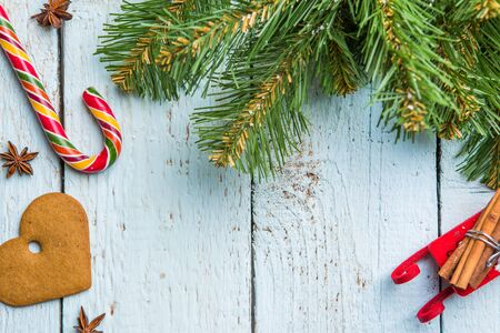 Christmas tree brunches, cookie and lollipop on white wooden boards. Christmas background.