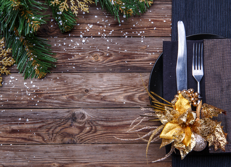 grunge cutlery: Christmas table place setting with black napkin, plate, fork and knife, decorated gold flower and christmas pine branches. Christmas holidays background.