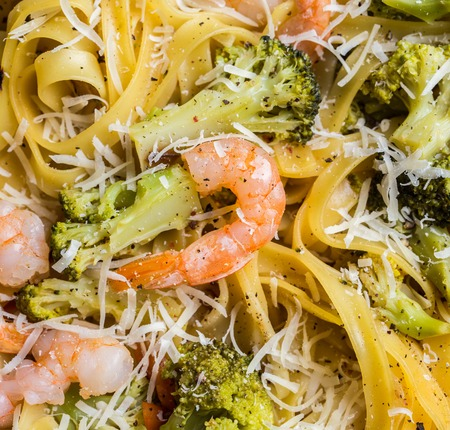 Close-up of pasta linguine with shrimps, broccoli, tomatto and cheese. Top view.