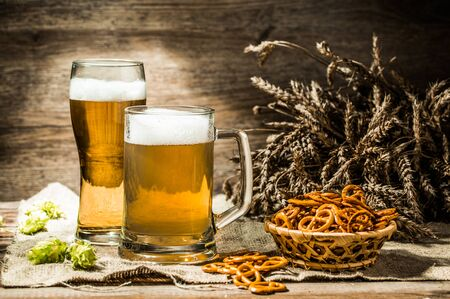 Mug, glass of beer on wooden table with wheat spikelets, hops and basket of pretzels