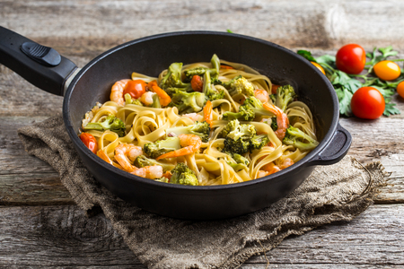 Pasta linguine with shrimps and broccoli in dripping pan on wooden background. Top view. Stock Photo