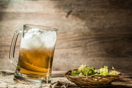 Frothy beer poured from cup standing on linen cloth on empty wooden background Stock Photo