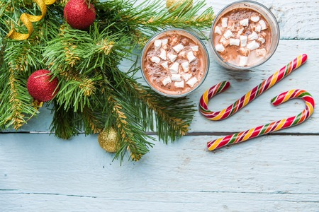 Two glasses of cocoa with marshmallows and christmas tree with toys on white wooden background. View from above
