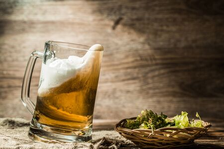 background next: Beer spills from tankard on empty wooden background next to hop in basket