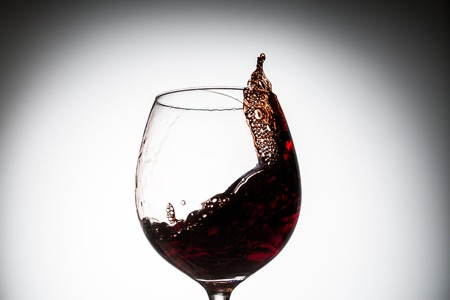 Stream of wine being pouring into a glass. Closeup splash of wine. Stock Photo
