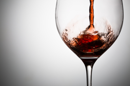 Red wine is poured on the wall of wineglass. Image with space for text