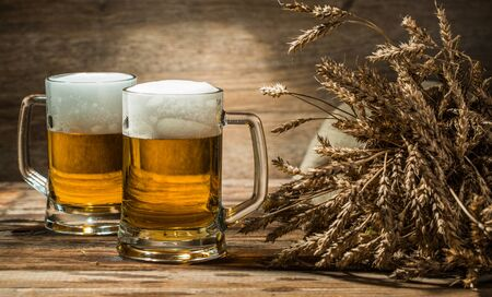 tankard: Wheat spikelets with two mugs of beer on empty wooden background Stock Photo