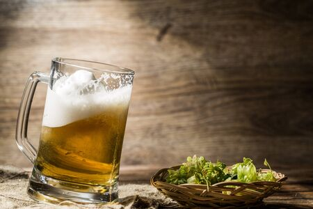 frothy: Frothy beer spills from tankard on empty wooden background next to hop in basket Stock Photo