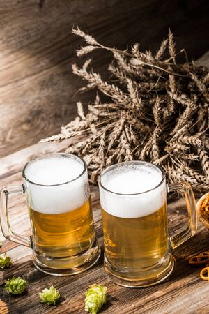 Mugs for beer, hops, wheat ears on empty wooden table, top view Stock Photo