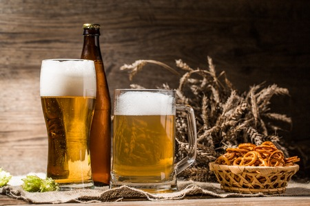 Mug, glasse, bottle of beer with foam close up with hop, pretzels and wheat