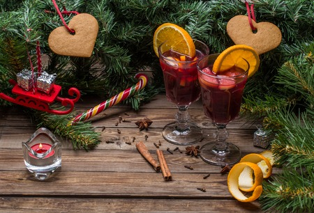 Two glasses of hot mulled wine with oranges, apples and spices. Christmas background.
