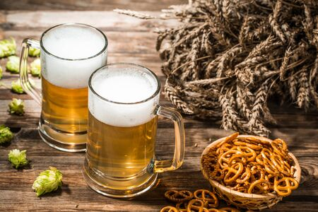 spikes: Two tankard beer, wheat spikes, hop on wooden table Stock Photo