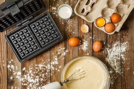 Making waffles at home - waffle iron, batter in bowl and ingredients - milk, eggs and flour. Cooking background. Stock Photo