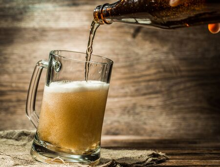 Foamy beer from bottle poured into mug standing on empty wooden background Stock Photo