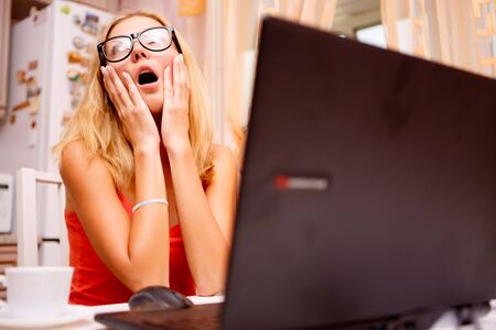 Young woman using her laptop and experiencing strong emotions, funny portrait at home