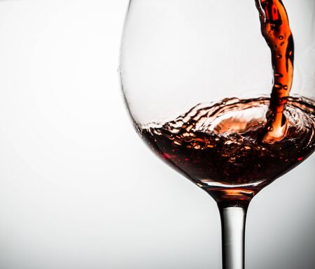 Grape wine poured into glasses on gray background empty