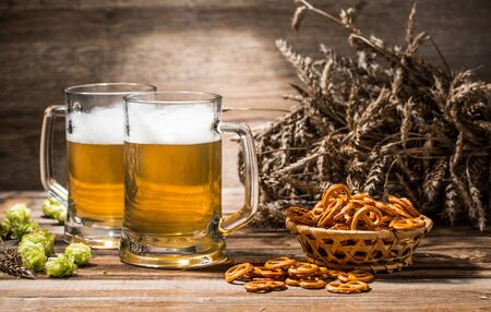 spikes: Photo of two mugs of beer with pretzels, wheat spikes, hops on wooden table Stock Photo