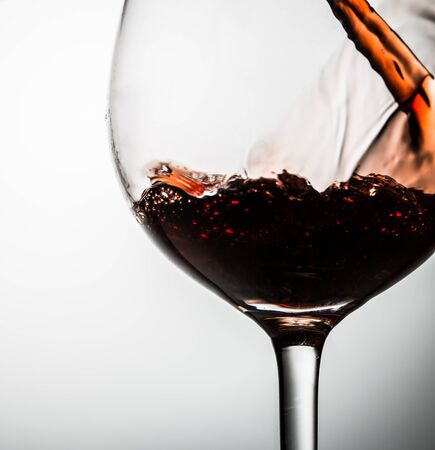 Glass on thin stalk on blank background with red wine