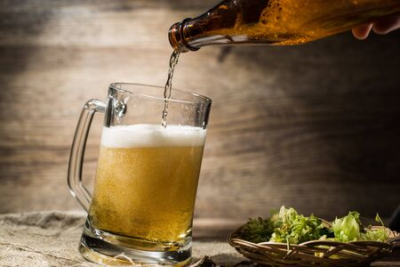 On empty wooden background beer flows from bottle in mug Stock Photo