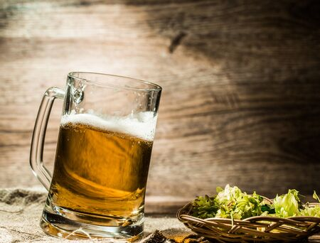 tankard: Big mug of beer stands on linen cloth with hops on table
