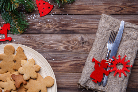 Table with cutlery decorated Christmas cookies, fir branches Stock Photo