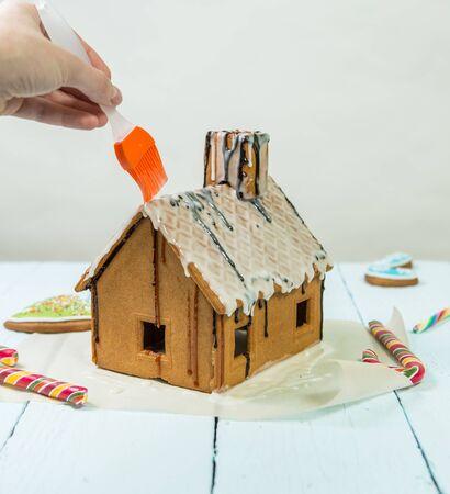 selebration: Glazing on homemade gingerbread house. Preparing for Christmas selebration Stock Photo