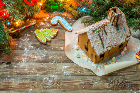 Homemade gingerbread house and christmas tree brunch with toys and garland.