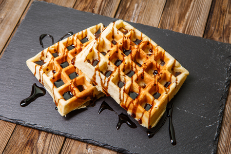 Photography of Viennese waffles watered by chocolate on wooden table