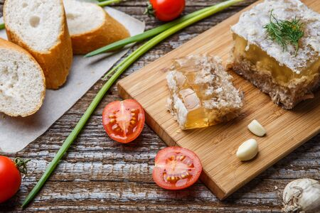 russian food: Homemade jelly meat with mustard, bread, tomatoes and garlic on the table. Holodets, traditional Russian food Stock Photo