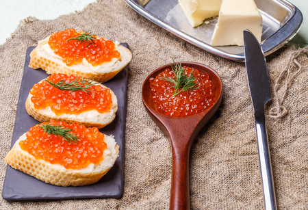 Sandwiches with red caviar, wooden spoon, butter knife on white wooden table