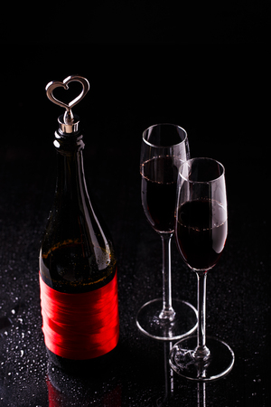 Bottle of wine with a cork in the form of heart and two glasses.