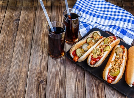 American hot dog with pickles,onions, ketchup, mustard and two soda Stock Photo