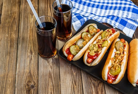 American hot dog with pickles,onions, ketchup, mustard and two soda on wood background