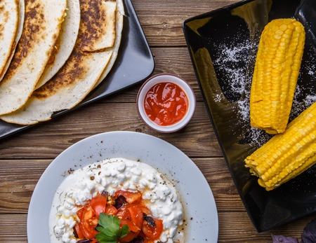 Quesadilla, salad with cottage cheese and tomatoes, two corn on wood table. Stock Photo