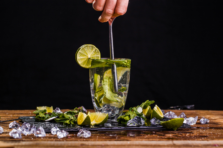 Glass of mojito, human hand Stock Photo