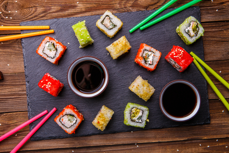 Sushi Set rolls with soy sauce served on gray stone slate