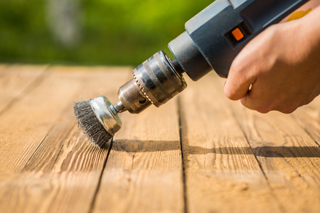 Hands man with electrical rotating brush metal disk sanding a piece of wood Stockfoto