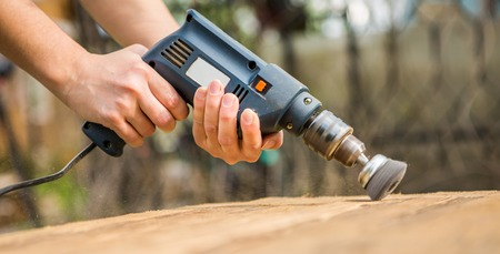 Hands man with electrical rotating brush metal disk sanding a piece of wood Stock Photo