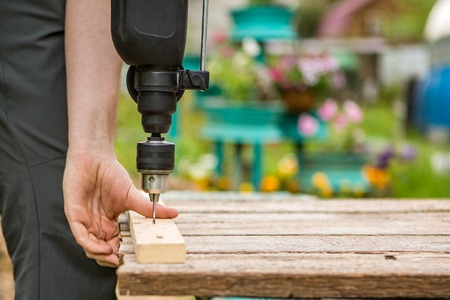 Worker fastens board with drill