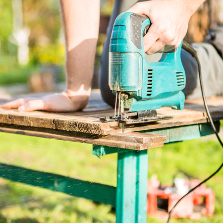 Man sawing plank in park with electric fret saws Stock Photo