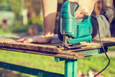Worker saws board in park