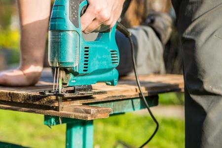 Employee working with electric jigsaw Stock Photo